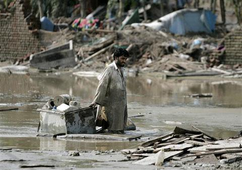 A flood survivor wades through mud as he salvages belongings in Azakhel, near Nowshera, northwest Pakistan, 14 Aug 2010